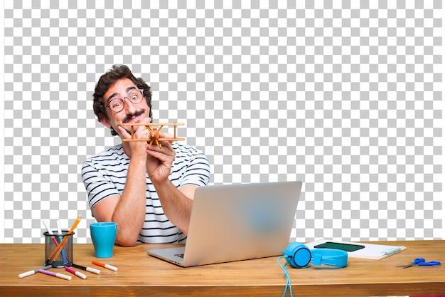 Jonge gekke grafische ontwerper op een bureau met laptop en met een houten vliegtuig Premium Psd
