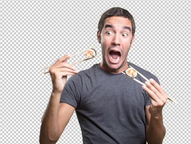 Jonge man die sushi eet Premium Psd