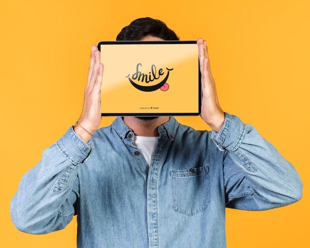 Jonge man die zijn gezicht bedekt met een tablet mock up Gratis Psd