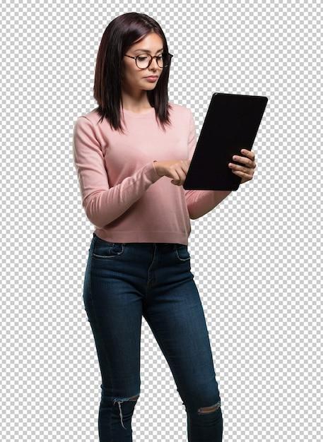 Jonge mooie vrouw glimlachend en zelfverzekerd, met een tablet, gebruiken om te surfen op het internet en sociale netwerken, communicatie te zien Premium Psd