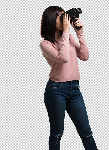 Jonge mooie vrouw opgewonden en vermaakt, kijkend door een filmcamera, op zoek naar een interessant schot, opname van een film, uitvoerend producent Premium Psd