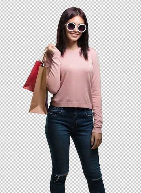 Jonge mooie vrouw vrolijk en glimlachend, erg opgewonden met boodschappentassen, klaar om te gaan winkelen en op zoek te gaan naar nieuwe aanbiedingen Premium Psd