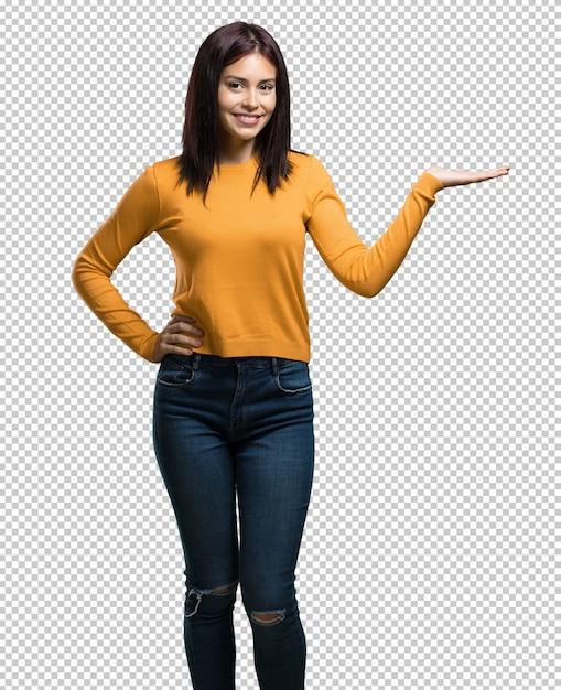 Jonge mooie vrouwenholding iets met handen, die een product tonen, glimlachend en vrolijk, die een denkbeeldig voorwerp aanbieden Premium Psd