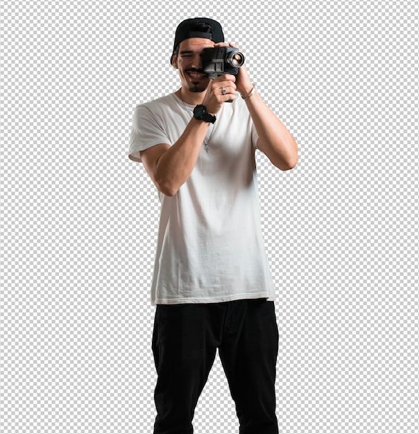 Jonge rapper man opgewonden en vermaakt, kijkend door een filmcamera, op zoek naar een interessant schot, een film opnemen, uitvoerend producent Premium Psd