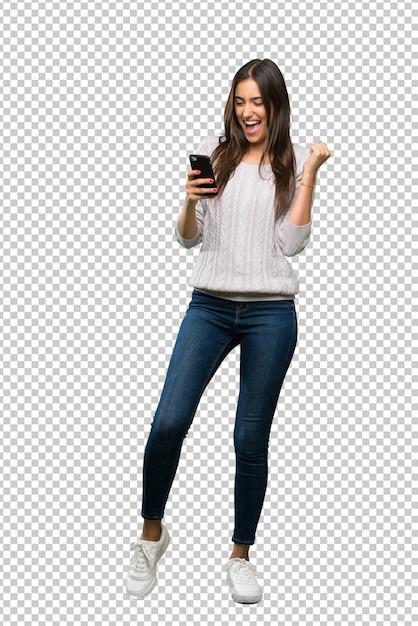 Jonge spaanse donkerbruine vrouw met telefoon in overwinningspositie Premium Psd