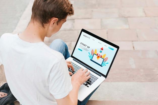 Jonge student die aan laptop in openlucht werkt Gratis Psd