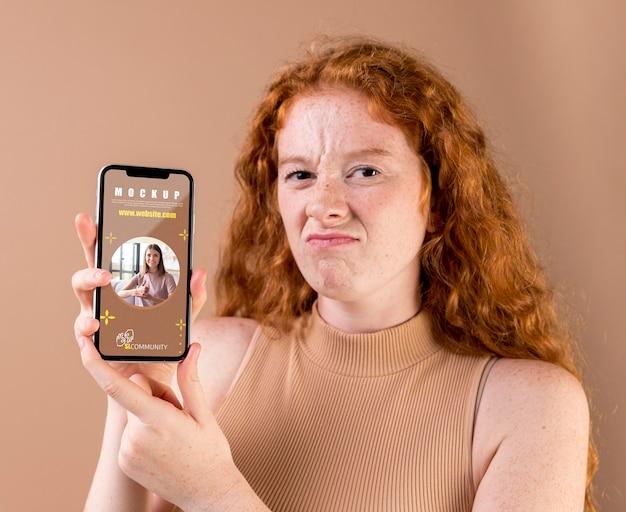 Jonge vrouw die een smartphonemodel houdt Premium Psd