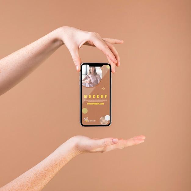 Jonge vrouw die een smartphonemodel houdt Gratis Psd