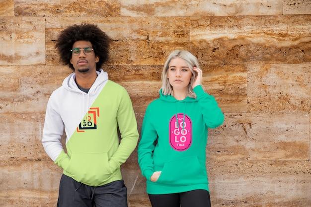 Jonge vrouw en man dragen hoodies Gratis Psd