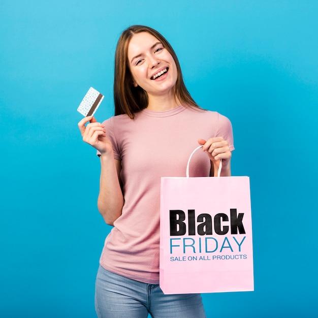 Jonge vrouw met een papieren zak en een creditcard Gratis Psd