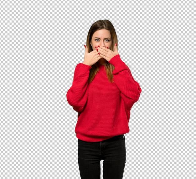 Jonge vrouw met rode sweater die mond behandelt met handen voor iets ongepast zeggen Premium Psd