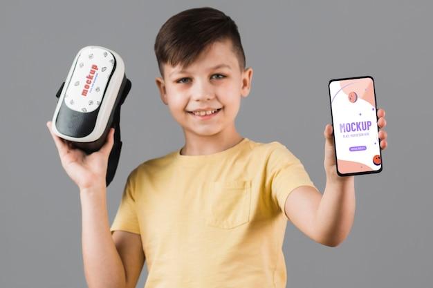 Jongen die virtuele werkelijkheidshoofdtelefoon met telefoonmodel houden Gratis Psd
