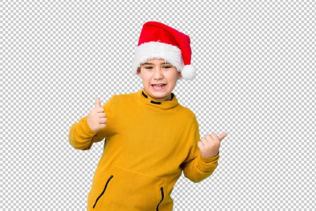 Jongetje vieren kerstdag dragen een kerstmuts verhogen beide duimen omhoog, glimlachen en zelfverzekerd. Premium Psd