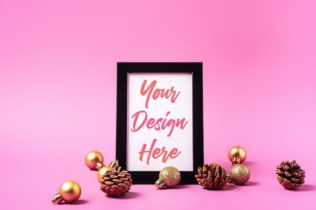 Kerst minimale compositie met leeg afbeeldingsframe. gouden ornament, dennenappels decoraties. mock up wenskaartsjabloon Premium Psd