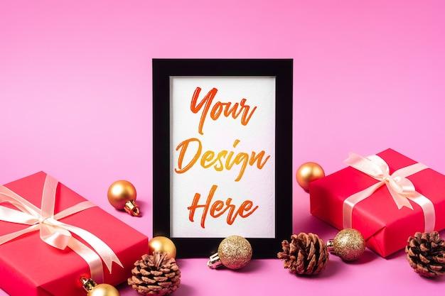 Kerst minimale compositie met leeg afbeeldingsframe. gouden ornament, geschenkdozen en dennenappels decoraties. mock up wenskaartsjabloon Premium Psd