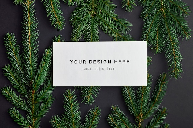 Kerst wenskaart mockup met fir tree takken op zwart Premium Psd