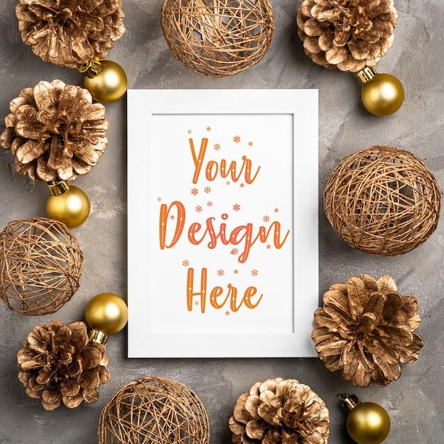 Kerstmissamenstelling met lege omlijsting. gouden ornament, dennenappels decoraties. mock up wenskaartsjabloon Premium Psd