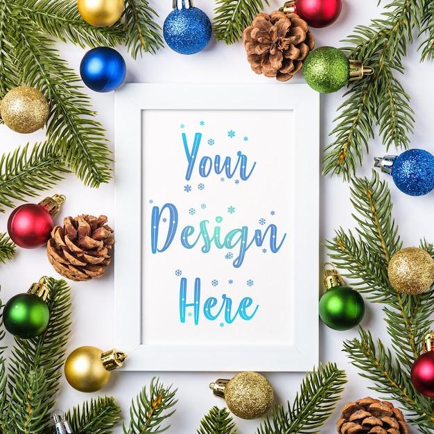 Kerstmissamenstelling met lege omlijsting. kleurrijk balornament, dennenappels en dennennaaldendecoraties. mock up wenskaartsjabloon Premium Psd