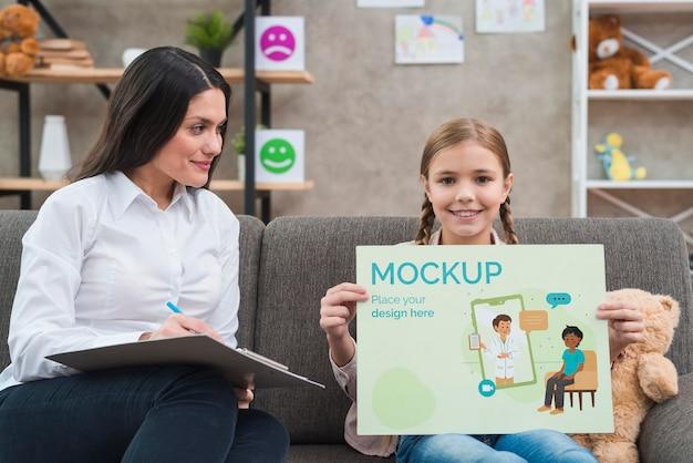 Kind en vrouw met een mock-up klembord vooraanzicht Gratis Psd