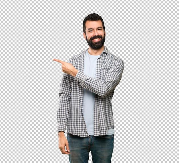 Knappe man met baard wijst naar de kant om een product te presenteren Premium Psd