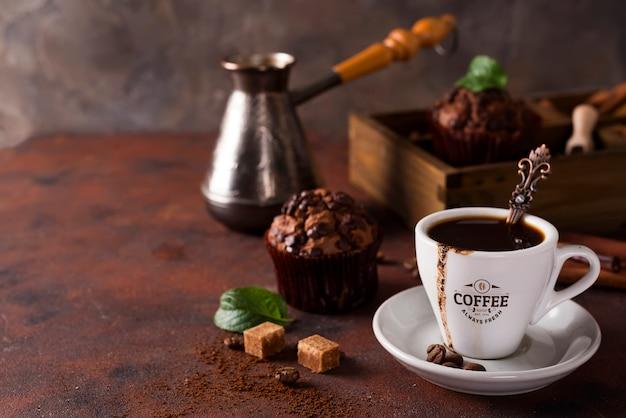 Kopje koffie met cooffee bonen, houten doos met korrels van koffie en specerijen, cupcake op een steen Premium Psd
