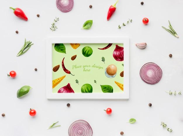 Kruiden mock-up frame omgeven door specerijen en plakjes groenten Gratis Psd
