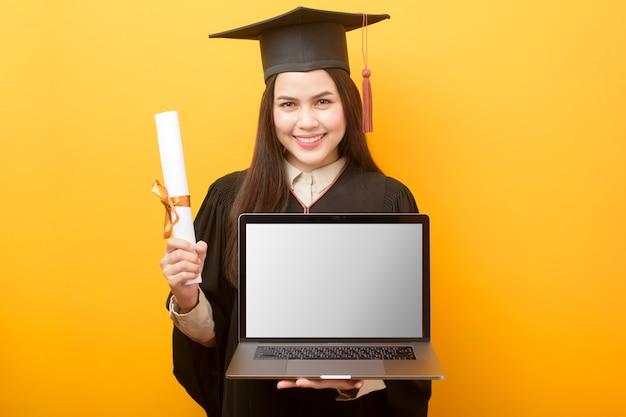 La bella donna in abito di laurea sta tenendo il modello del computer portatile Psd Premium