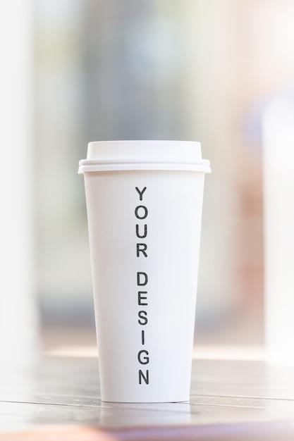 La tazza e lo smartphone di caffè a gettare sulla tavola di legno al caffè del caffè hanno offuscato il fondo Psd Premium