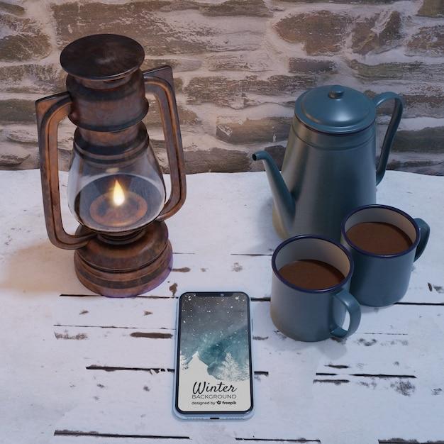 Lantaarn en waterkoker met hete thee naast mobiel Gratis Psd
