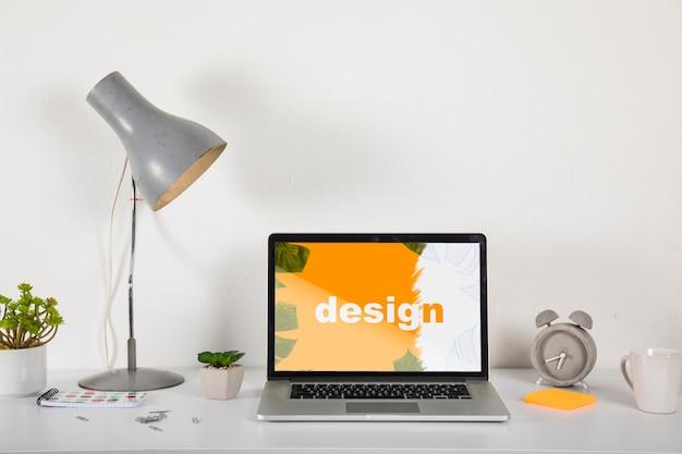 Laptop mockup op bureau met elementen Gratis Psd