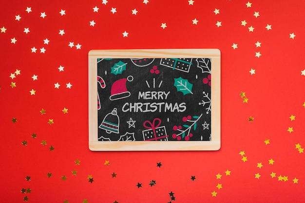 Lay flat de pizarra de concepto de navidad con fondo rojo. PSD gratuito