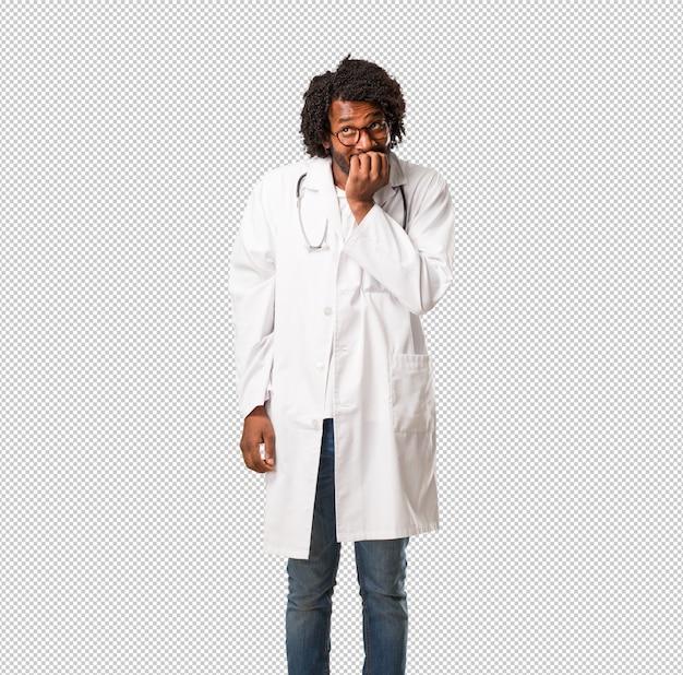 Le belle unghie mordaci del dottore afroamericano, nervose, molto ansiose e spaventate per il futuro, provano panico e stress Psd Premium