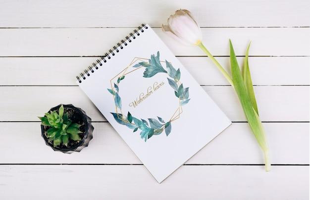 Lente notebook mockup met decoratieve plant in bovenaanzicht Gratis Psd
