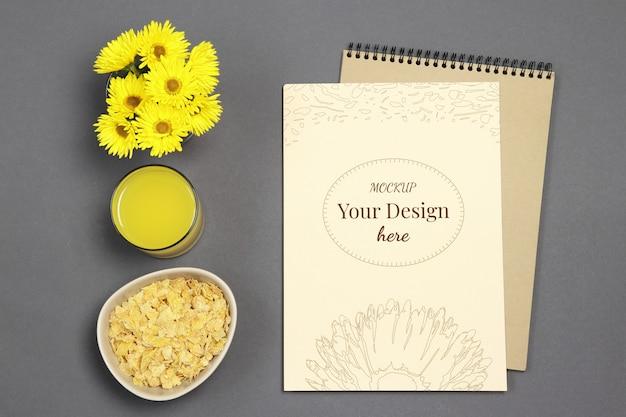 Lettera di mockup su sfondo grigio con fiori gialli, succo fresco e fiocchi Psd Premium