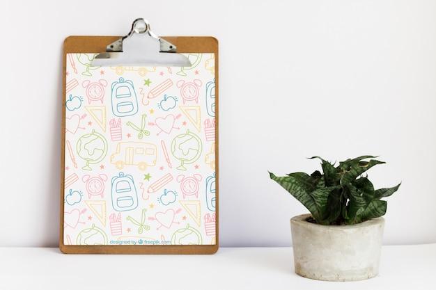 Leunend klembord naast een plant Gratis Psd