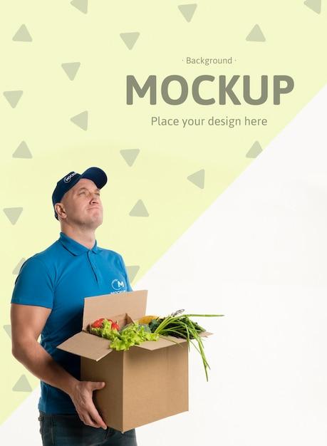Levering man met een doos met verschillende groenten Gratis Psd