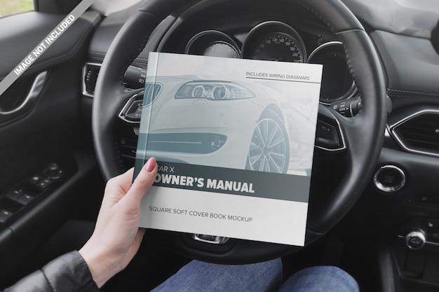 Libro quadrato nella mano della ragazza sul modello del volante dell'automobile Psd Premium