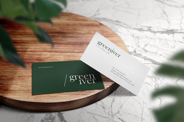 Limpie la maqueta mínima de la tarjeta de visita en la tabla circular de madera y la sombra verde de las hojas. PSD Premium