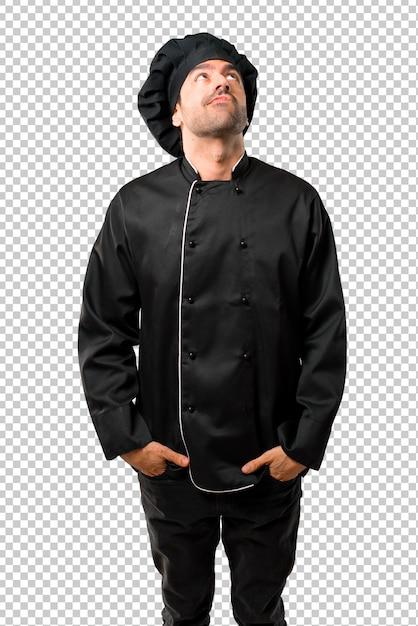 Lo chef in uniforme nera stand e guardando con faccia seria Psd Premium