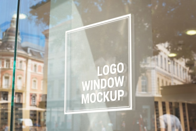 Logo, teken mockup op glazen winkelvenster. stadsgebouwen op achtergrond Premium Psd