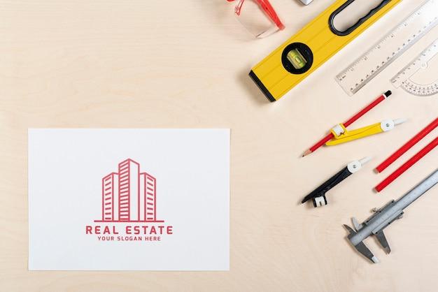 Logotipo inmobiliario con edificios y artículos de papelería PSD gratuito