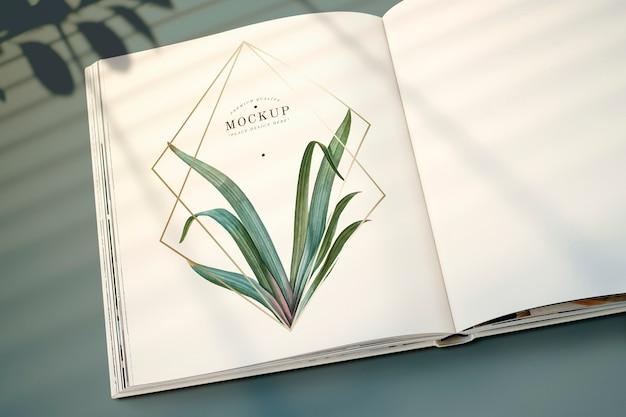 Magazine mockup met bladeren en gouden frame Gratis Psd