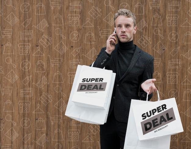 Man met boodschappentassen praten aver telefoon Gratis Psd