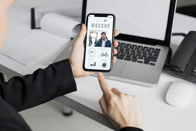 Man met een smartphone-mock-up op kantoor Gratis Psd