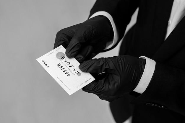 Man met handschoenen met een visitekaartje mock-up Gratis Psd