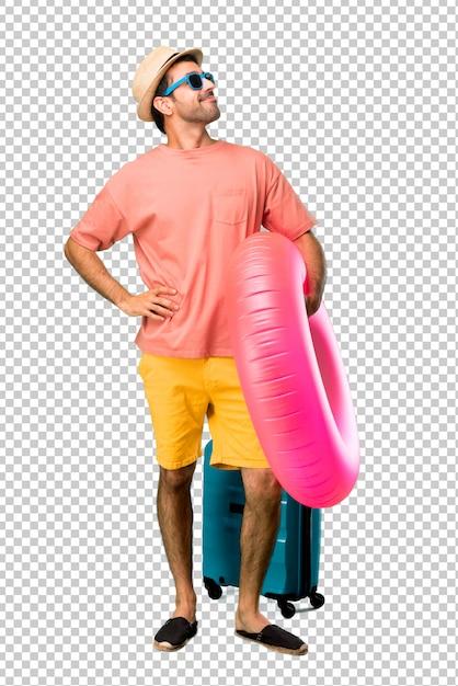Man met hoed en zonnebril op zijn zomervakantie poseren met armen op heup en lachen Premium Psd