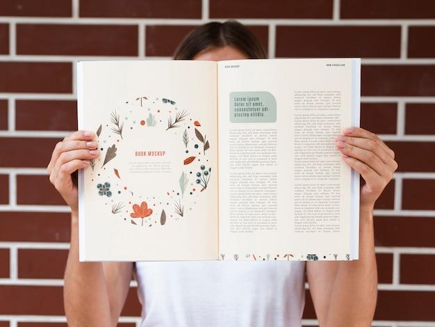 Mani che mostrano una rivista di natura mock up Psd Gratuite