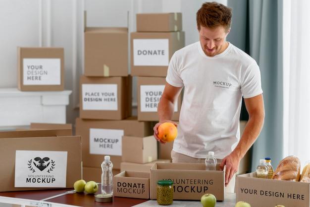 Mannelijke vrijwilliger die donatiebox met bepalingen voorbereidt Gratis Psd