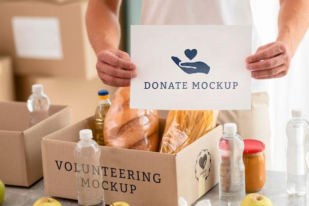 Mannelijke vrijwilliger met blanco papier met doos met voedsel voor donatie Gratis Psd