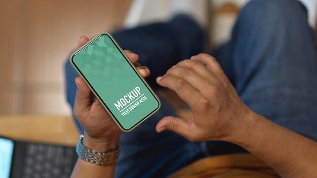Mannenhand mockup smartphone gebruikt zittend in de kantoorruimte Premium Psd